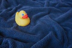 在蓝色波浪毛巾的一只黄色橡胶鸭子 免版税库存照片