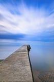 在蓝色海和多云天空的具体码头或跳船。 诺曼底,法国 库存照片