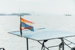 在蓝色海天空的老泰国旗子 损坏退色 免版税库存照片