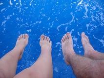在蓝色海水上的女性和男性脚,夏天 库存照片