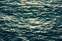 在蓝色海波浪水的闪耀的光 库存照片