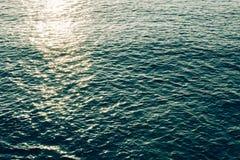 在蓝色海波浪水的闪耀的光 免版税库存图片