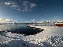 在蓝色海湾和多雪的山的日出与老码头 免版税库存照片