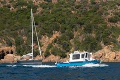 在蓝色海的帆船在可西嘉岛海岛,法国海岸的一个海湾的  库存图片
