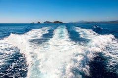在蓝色海的波浪在小船后 库存照片