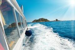 在蓝色海的波浪在小船后 免版税库存照片