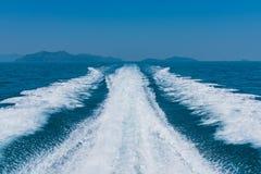 在蓝色海的波浪在有山和天空的速度小船后 库存照片