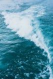 在蓝色海的波浪在速度小船后 免版税图库摄影