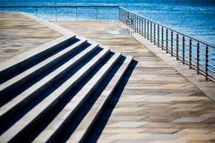 在蓝色海的石码头有发光的栏杆的 免版税库存图片