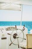 在蓝色海背景的方向盘白色游艇  库存图片
