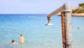在蓝色海背景的海滩阵雨 免版税库存照片