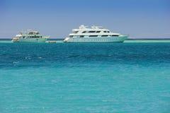 在蓝色海背景的游艇 库存图片