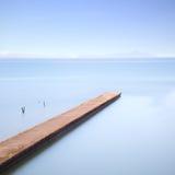 在蓝色海运的具体码头或跳船。 在背景的小山 免版税库存照片