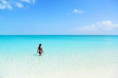 在蓝色海洋使假日比基尼泳装妇女游泳靠岸 库存照片
