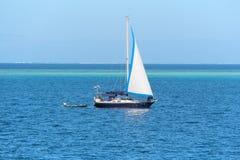 在蓝色海洋水的小船 库存图片