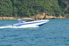 在蓝色海水的白色速度小船 库存图片