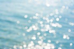 在蓝色海水纹理背景的抽象光亮的阳光bokeh 图库摄影