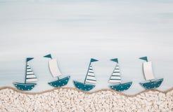 在蓝色海洋背景的五条金属手工制造风船总和的 图库摄影