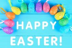 在蓝色淡色木背景的五颜六色的复活节彩蛋与空间 愉快的复活节 库存照片