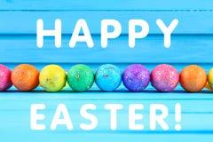 在蓝色淡色木背景的五颜六色的复活节彩蛋与空间 愉快的复活节 免版税图库摄影