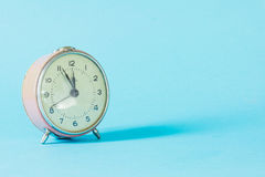 在蓝色淡色背景的减速火箭的闹钟时间 免版税图库摄影