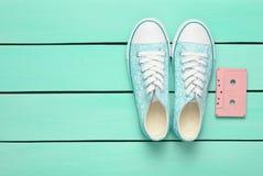 在蓝色淡色背景的卡型盒式录音机和运动鞋鞋子 古板的技术 免版税库存照片