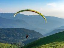 在蓝色清楚的天空的黄色滑翔伞在绿色山 库存图片
