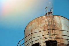 在蓝色清楚的天空背景的老和生锈的水塔  库存图片