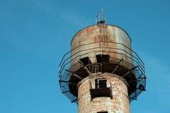在蓝色清楚的天空背景的老和生锈的水塔  免版税库存照片