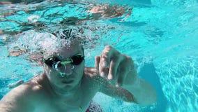 在蓝色清楚的水池的年轻人游泳 股票录像