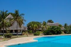 在蓝色清楚的水池附近的美丽的豪华村庄房子 免版税图库摄影