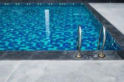 在蓝色游泳池旁边的扶手栏杆 免版税库存照片