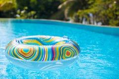 在蓝色游泳水池的五颜六色的水池浮游物 库存照片