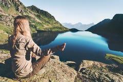 在蓝色湖的女子思考的瑜伽 免版税图库摄影
