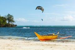 在蓝色热带海的黄色在海洋Philippiness的小船和kiters 图库摄影
