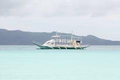 在蓝色热带海,菲律宾博拉凯的大白色汽船我 图库摄影