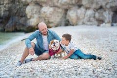 在蓝色焰晕的牛仔裤人穿戴的英俊大胆时髦坐海滩海边与逗人喜爱的儿子男孩青少年的andpretty engli一起 免版税库存图片