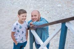 在蓝色焰晕的牛仔裤人穿戴的英俊大胆时髦坐海滩海边与逗人喜爱的儿子男孩青少年的andpretty engli一起 库存照片
