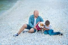 在蓝色焰晕的牛仔裤人穿戴的英俊大胆时髦坐海滩海边与逗人喜爱的儿子男孩青少年的andpretty engli一起 库存图片