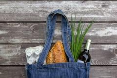 在蓝色牛仔布市场袋子的新鲜农产品在木背景,平的位置 Eco友好的可再用的购物带来为使废物减到最小, 库存图片
