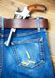 在蓝色牛仔裤他的传送带的左轮手枪  库存图片