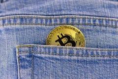 在蓝色牛仔裤口袋的Bitcoin硬币 免版税图库摄影