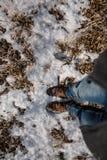 在蓝色牛仔裤和冬天鞋子的男性腿在雪,特写镜头 免版税库存图片