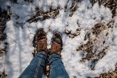 在蓝色牛仔裤和冬天鞋子的男性腿在雪,特写镜头 免版税库存照片