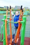在蓝色牛仔裤和无袖的夹克打扮的小女孩参与在运动场的体育模拟器 免版税库存图片