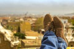 在蓝色牛仔裤和棕色鞋子的妇女脚在城市` s模糊的背景放松 库存照片