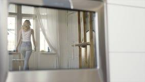 在蓝色牛仔裤和白色无袖衫的在家走到窗口的一名亭亭玉立的白肤金发的妇女的镜子的反射 r 免版税库存照片