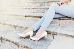 在蓝色牛仔裤和米黄亮漆鞋子的典雅的女性腿在sta 免版税库存图片