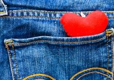 在蓝色牛仔裤的一个口袋的红色心脏 免版税库存图片