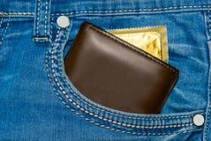 在蓝色牛仔裤的一个口袋的钱包有金避孕套的 库存图片